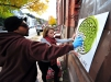 "Yasir Ahmed, of Ewing and A'ine Mickey, Of Trenton stencil a ""Flower of Life"" onto a vacant building in Trenton's Wilbur Section on Saturday Oct. 17, 2015. (Scott Ketterer - The Trentonian)"