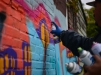 Leon Rainbow works on large mural at the Windows Of Soul event on the 100 block of Walnut Avenue in Trenton on Saturday Oct. 17, 2015. (Scott Ketterer - The Trentonian)